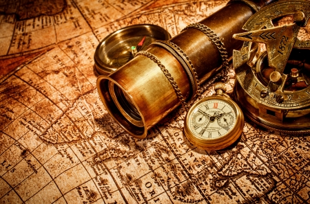 bygone: Vintage compass, , spyglass and a pocket watch lying on an old map.