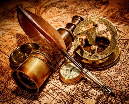 ビンテージ コンパス、ガチョウのクイル ペン、スパイグラス、古い地図の上に横たわる懐中時計。