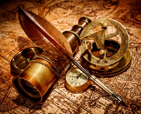 Vintage compass, goose quill pen, spyglass and a pocket watch lying on an old map. photo