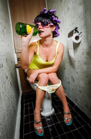 borracha: chica se sienta en un inodoro con una botella de alcohol