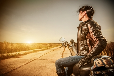motor bike: Biker girl in a leather jacket on a motorcycle looking at the sunset.