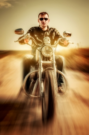 Biker in a leather jacket riding a motorcycle on the road photo