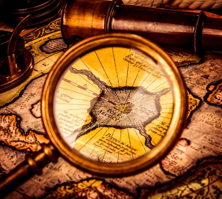 charred: Vintage magnifying glass lies on the ancient map of the North Pole (also Hyperborea). Arctic continent on the Gerardus Mercator map of 1595.