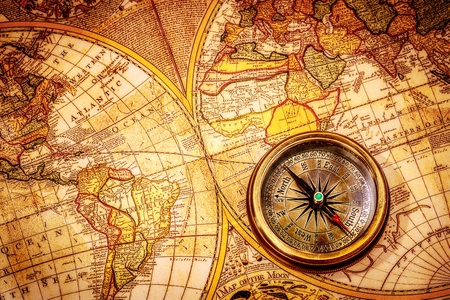 antiquity: Vintage still life. Vintage compass lies on an ancient world map.