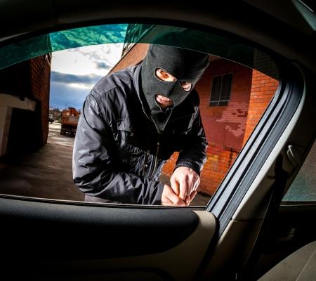 robo de autos: El ladrón y el ladrón de autos en una máscara que se abre la puerta del coche y se secuestra el coche.