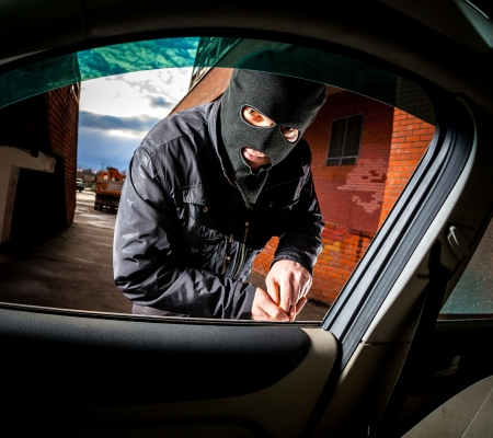 thieves: Robber and the car thief in a mask opens the door of the car and hijacks the car.