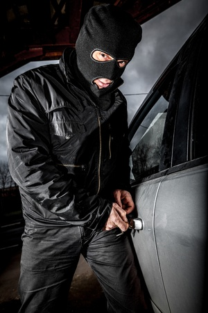 Robber and the car thief in a mask opens the door of the car and hijacks the car. photo