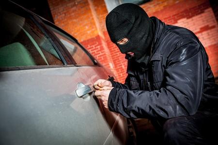 robo de autos: El ladr?n y el ladr?n de autos en una m?scara que se abre la puerta del coche y se secuestra el coche.