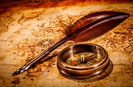Vintage magnifying glass and compass lying on an old map. photo
