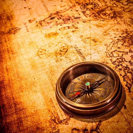 business direction: Vintage still life. Vintage compass lies on an ancient world map.
