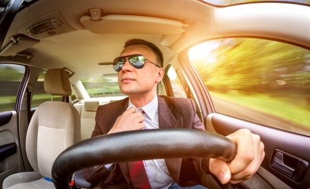 Man in a suit and sunglasses driving on a road in the car. photo