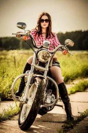 moteros: Muchacha del motorista con gafas de sol sentado en motocicleta