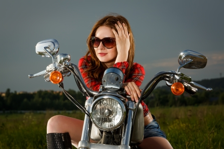 motors: Biker girl with sunglasses sitting on motorcycle