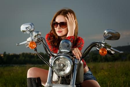 pantalones cortos: Muchacha del motorista con gafas de sol sentado en motocicleta