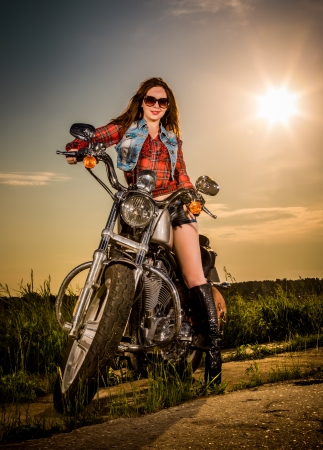 Biker girl with sunglasses sitting on motorcycle photo