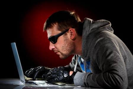 Hacker in a sunglasses with laptop. photo