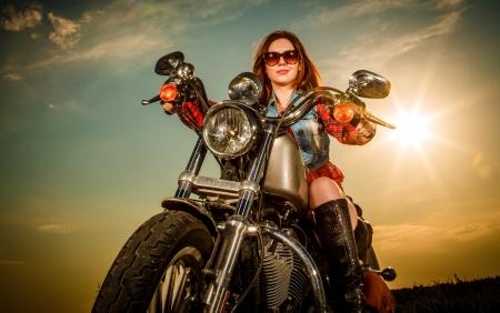 motorrad frau: Biker M?dchen mit Sonnenbrille sitzt auf dem Motorrad