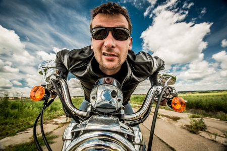 Biker in sunglasses and leather jacket racing on the road photo
