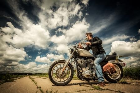 moteros: Biker en gafas de sol y chaqueta de cuero en el camino
