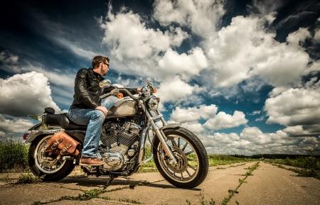motociclista: Biker en gafas de sol y chaqueta de cuero en el camino