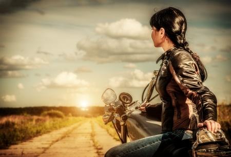 Muchacha del motorista en una chaqueta de cuero sobre una moto mirando la puesta de sol Foto de archivo - 21000288