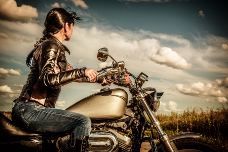 Biker girl in a leather jacket on a motorcycle looking at the sunset  photo