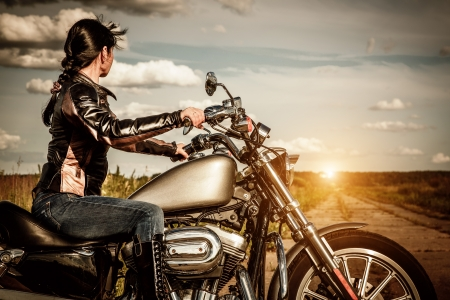 Biker girl in a leather jacket on a motorcycle looking at the sunset