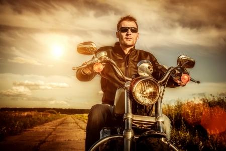 motociclista: Hombre del motorista con una chaqueta de cuero y gafas de sol sentado en su moto mirando la puesta de sol Foto de archivo