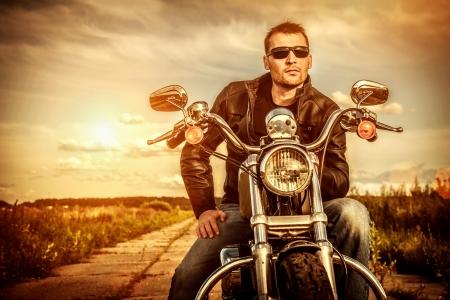 Biker man draagt een leren jas en zonnebril zitten op zijn motor te kijken naar de zonsondergang