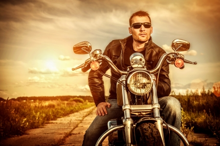 Biker man wearing a leather jacket and sunglasses sitting on his motorcycle looking at the sunset  Фото со стока