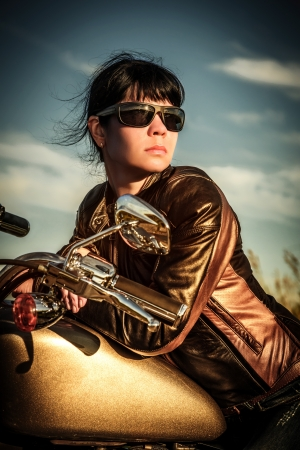 motorcycle wheel: Biker girl in a leather jacket on a motorcycle looking at the sunset