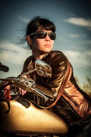 moteros: Muchacha del motorista en una chaqueta de cuero sobre una moto mirando la puesta de sol