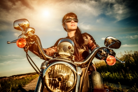 bikers: Biker girl in a leather jacket on a motorcycle looking at the sunset