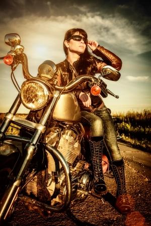 Biker Mädchen in einer Lederjacke auf einem Motorrad Blick auf den Sonnenuntergang
