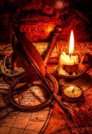 bygone: Vintage compass, magnifying glass, pocket watch, quill pen, spyglass lie on an old ancient map with a lit candle  Vintage still life