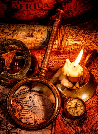 Vintage compass, magnifying glass, pocket watch, spyglass lie on an old ancient map with a lit candle  Vintage still life  photo