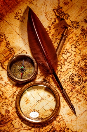 Vintage magnifying glass, compass, goose quill pen, spyglass lying on an old map. photo