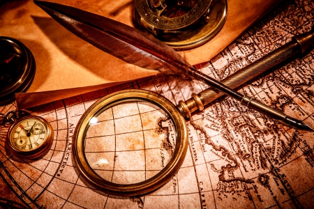 geography: Vintage magnifying glass, compass, goose quill pen, spyglass and a pocket watch lying on an old map. Stock Photo
