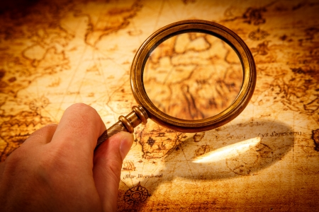 magnifying: Vintage still life. Vintage magnifying glass lies on an ancient world map
