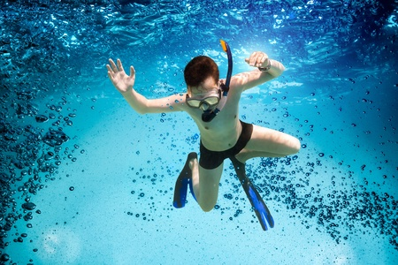 Freedive. Teenager in the mask and snorkel swim underwater. photo