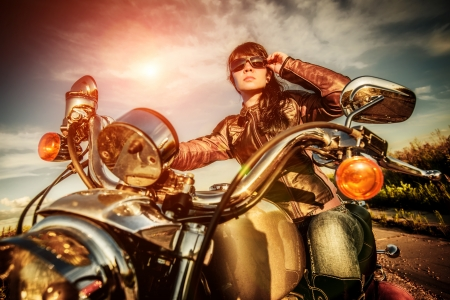 moteros: Muchacha del motorista en una chaqueta de cuero en una motocicleta mirando la puesta de sol. Foto de archivo