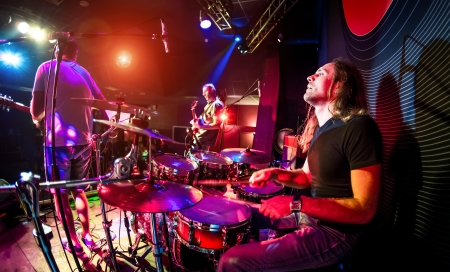 Performances of the musicians, the drummer in the foreground, rock music concert Stock Photo