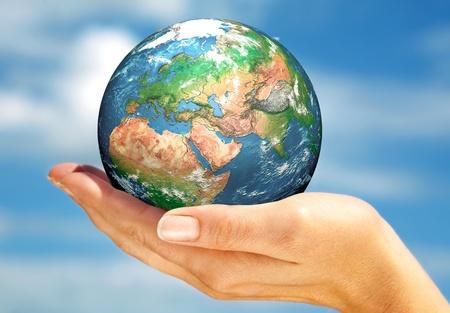 Human hand holding a globe.