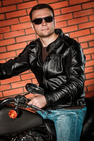 Biker in sunglasses and a leather jacket on a motorcycle photo
