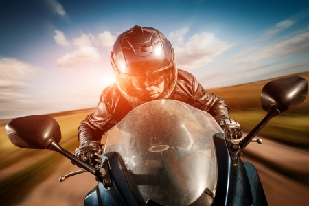 speed: Biker in helmet and leather jacket racing on the road Stock Photo