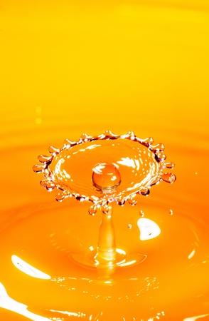 Drop of orange juice close up photo