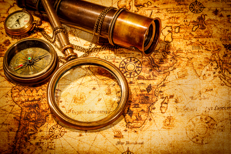 telescope: Vintage magnifying glass, compass, telescope and a pocket watch lying on an old map.