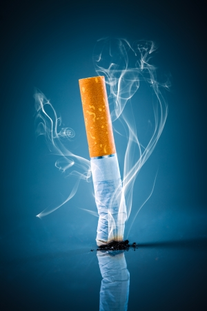no fumar: No fumar. Colilla de cigarrillo en un fondo azul.