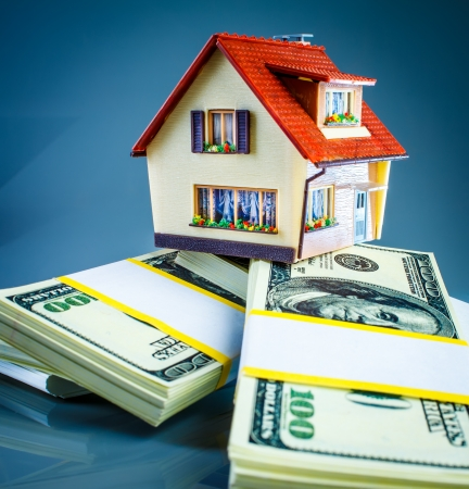 refinance: house on packs of banknotes on a blue background.