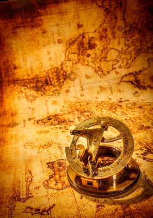 Vintage still life. Vintage compass lies on an ancient world map. Stock Photo - 22219924